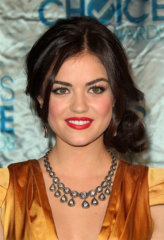 Hairstyles for Round Faces with Bangs  Isn't Lucy Hale pretty as a button with that round face of hers? And she sure knows what she's doing with her hair. Here, she's gone for a low bun that sits nicely on the side of her head. Her prominent bangs in the front hide the width of her face and make it look less round.