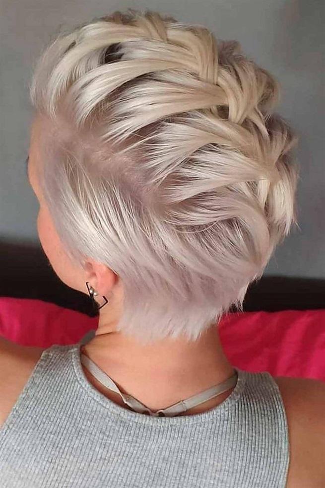 Kurze Frisuren Frauen Platin Farbe  Kann ein Mohawk weiblich sein? Sicherlich, wie Frauen es erfolgreich angenommen haben und der Welt ihre mädchenhafte Seite zeigen. Aber kann es auf kurzen Haaren weiblich sein? Nun, dieses Bild ist ein Beweis. Sobald Sie Ihr Oberteil abgetrennt und zu einem entspannten niederländischen Geflecht geflochten haben, das sich entlang des Haaransatzes bewegt, werden Sie dem heißesten Mohawk-inspirierten Look aller Zeiten Leben einhauchen! Da der Stil ziemlich locker ist, empfehlen wir Ihnen, ihn mit einer dicken Schicht Haarspray zu bestreichen.