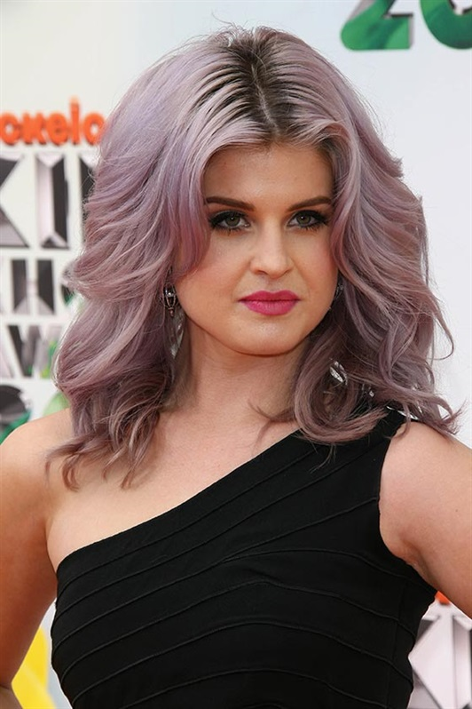 Long Hairstyles for Round Faces with Colorful Hairs  Now here's a look that's bound to turn you into a total bomb. Kelly Osbourne went for a wavy style with oodles of volume that hides most of her cheeks. Parted in the center, her waves fit perfectly on her cheekbones and alter the round shape of her face.