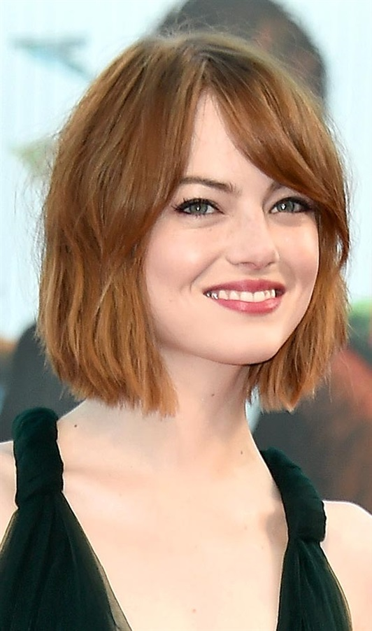 Mid Bob Hairstyles for Round Faces and Fire Red Hair Colour  The short bob is a classic. But listen, my round-faced girl friends! We must avoid the classic version of this look because it accentuates the roundness of the face.  But do not worry! The classic bob is not the only type of bob that exists. For us women with a round face, an angled bob is the way to go. In this hairstyle, the front layers are sweeping the chin dramatically while the back layers are short. The hairstyle gives a structured look and the hard lines of the bob balance the soft lines of the round face and make it slimmer.