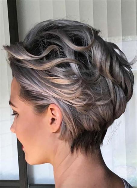 Kurze Haare Wellig und Locken  Wellenförmige Frisuren können beim Zurückfegen eine zusätzliche Glätte erhalten, ohne ihre leichte Locke zu verlieren. Der eisgraue Farbton sorgt für zusätzliche Kühle, wobei die Dimension dank der dunklen Wurzeln erscheint.